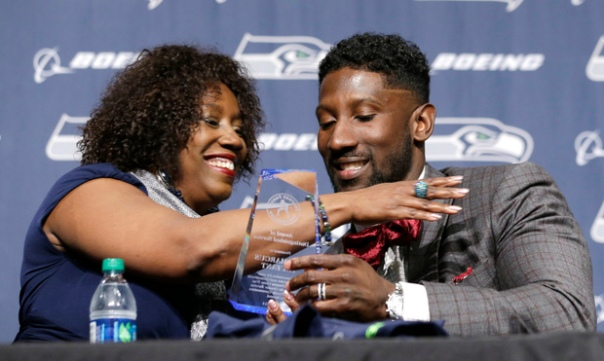Seattle Seahawks' Marcus Trufant, left, is embraced by his mother, Constance Trufant, as she presented him with an award from the Trufant Family Foundation at a news conference announcing his retirement from football after signing with the team a day earlier, Thursday, April 24, 2014, in Renton, Wash. Trufant started 125 games in a Seattle career that lasted from 2003 to 2012. The cornerback was a first-round pick in 2003 out of Washington State and immediately moved into the starting lineup, playing a key role on the 2005 team that advanced to the franchise's first Super Bowl. (AP Photo/Elaine Thompson)
